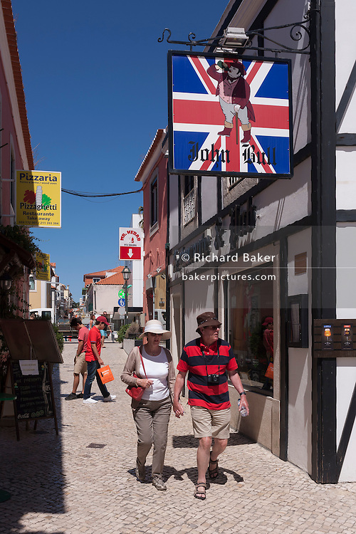 Two tourists walk beneath the sign to the John Bull, a British theme pub on 12th July 2016, at Cascais, near Lisbon, Portugal. John Bull is a national personification of the United Kingdom in general and England in particular, especially in political cartoons and similar graphic works. He is usually depicted as a stout, middle-aged, country dwelling, jolly, matter-of-fact man. Cascais is a coastal town and a municipality in Portugal, 30 kilometres (19 miles) west of Lisbon. The former fishing village gained fame as a resort for Portugal's royal family in the late 19th century and early 20th century. Nowadays, it is a popular vacation spot for both Portuguese and foreign tourists and located on the Estoril Coast also known as the Portuguese Riviera. (Photo by Richard Baker / In Pictures via Getty Images)
