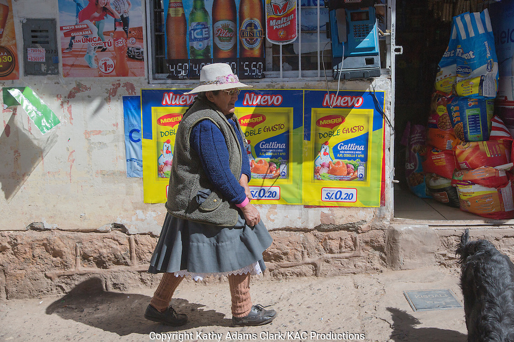 Lady in traditional dress in Cusco, Peru, walking in front of a small neighborhood store.
