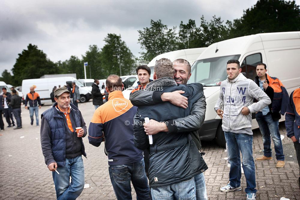 Nederland, Amsterdam , 28 juni 2013.<br /> Akkoord tussen bezorgers PostNL en de leidinggevenden van PostNL.<br /> ostNL heeft een onderhandelingsakkoord bereikt met FNV Bondgenoten en vertegenwoordigers van de actievoerende chauffeurs. Dat heeft een woordvoerder vrijdag laten weten.<br /> PostNL had een conflict met de chauffeurs, die als zelfstandige voor het postbedrijf werken, over onder meer de nieuwe, lagere tarieven voor de bezorging van pakketten. Maar nu is afgesproken dat de chauffeurs 1000 euro per week ontvangen, bij gemiddeld 145 tot 155 geplande stops per dag. Op routes met minder dan 145 adressen zal er 'maatwerk' plaatsvinden, aldus PostNL.<br /> Op de foto: Blijde pakketbezorgers van PostNL omhelzen elkaar na het bericht omtrent het akkoord.<br /> Foto:Jean-Pierre Jans