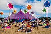 Its friday and its the orange wig - a visitor has a different colour for each day! A sculpture of coloured umbrellas provides a focal point in teh Arena - The 2018 Latitude Festival, Henham Park. Suffolk 13 July 2018