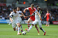 Southampton 's Sam Gallagher is tackled by Swansea's Jordi Amat (l) and Dwight Tiendalli .. Barclays Premier league match, Swansea city v Southampton at the Liberty stadium in Swansea, South Wales on Saturday 3rd May 2014.<br /> pic by Andrew Orchard, Andrew Orchard sports photography.