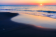 The curve of a receding wave reflects the sunrise on an Outer Banks beach in Corolla, NC.