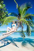 Woman relaxing on a palm tree on Nanuya Lailai island, the blue lagoon, Yasawas, Fiji, South Pacific, MR
