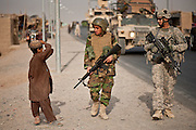 "An Afghan boy watches an American soldier and an Afghan soldier on patrol as part of a ""shonna b' shonna,"" or shoulder-to-shoulder, training program."