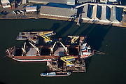 Nederland, Amsterdam, Mercuriushaven, 10-01-2009; Fosfaatweg, haven Amsterdam, overslag met drijvende kranen (of bokken) van zeeschip (coaster) naar binnenvaartschip (lichters); port of  Amsterdam, transhipment  with floating cranes from ship (coaster) to barges; veevoer, tapioca. .luchtfoto (toeslag); aerial photo (additional fee required); .foto Siebe Swart / photo Siebe Swart
