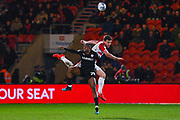 Andrew Butler of Doncaster Rovers (6) heads above Victor Adeboyejo of Barnsley (29) during the EFL Sky Bet League 1 match between Doncaster Rovers and Barnsley at the Keepmoat Stadium, Doncaster, England on 15 March 2019.