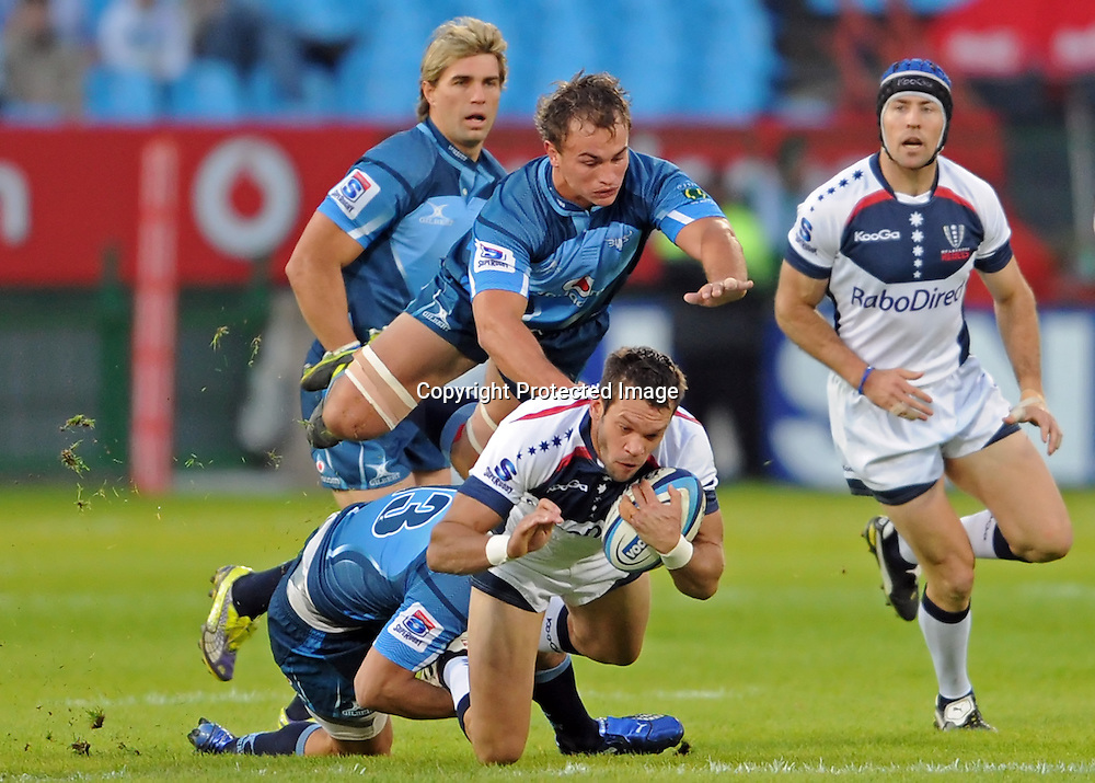 PRETORIA, South Africa, 14 May 2011. Luke Rooney of the Melbourne Rebels is tackled by Stephan Dippenaar and a flying Deon Stegmann of the Bulls during the Super15 Rugby match between the Bulls and the Melbourne Rebels at Loftus Versfeld in Pretoria, South Africa on 14 May 2011.<br /> Photographer : Anton de Villiers / SPORTZPICS