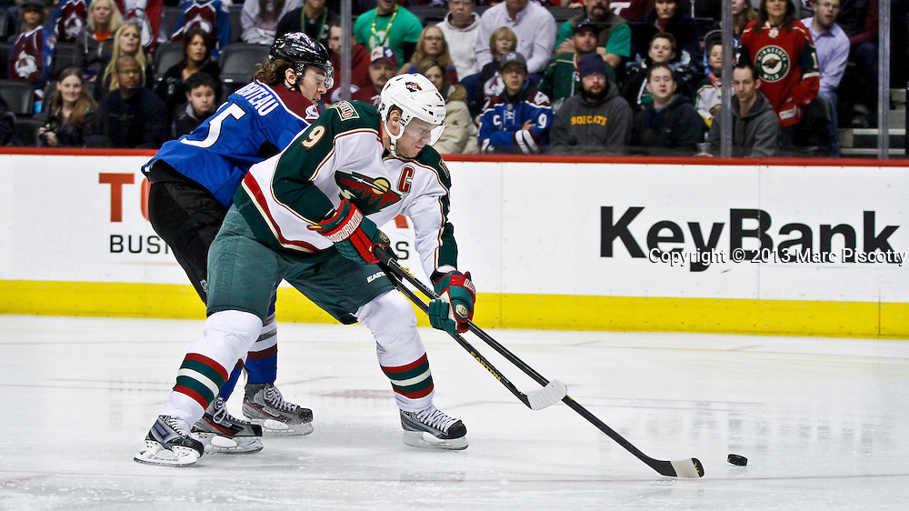 SHOT 3/16/13 1:14:53 PM - The Minnesota Wild's Mikko Koivu #9 fights for a loose puck with the Colorado Avalanche's P.A. Parenteau #15 during their regular season NHL game at the Pepsi Center in Denver, Co. The Minnesota Wild won the game 6-4. (Photo by Marc Piscotty / © 2013)