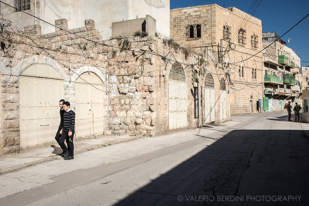 Jewish settlers walk on an army controlled street in the Area H2 (under full Israel control) of Hebron city centre in the West Bank. The closed gates used to be Arab shops. IDF shut them and Palestininans are not allowed to walk here anymore.