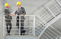 Full length of young male architect discussing on stairway