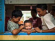 26 OCTOBER 2015 - YANGON, MYANMAR: A family on the Yangon Circular Train in the Yangon Central Station. The Yangon Circular Railway is the local commuter rail network that serves the Yangon metropolitan area. Operated by Myanmar Railways, the 45.9-kilometre (28.5 mi) 39-station loop system connects satellite towns and suburban areas to the city. The railway has about 200 coaches, runs 20 times daily and sells 100,000 to 150,000 tickets daily. The loop, which takes about three hours to complete, is a popular for tourists to see a cross section of life in Yangon. The trains run from 3:45 am to 10:15 pm daily. The cost of a ticket for a distance of 15 miles is ten kyats (~nine US cents), and for over 15 miles is twenty kyats (~18 US cents).     PHOTO BY JACK KURTZ