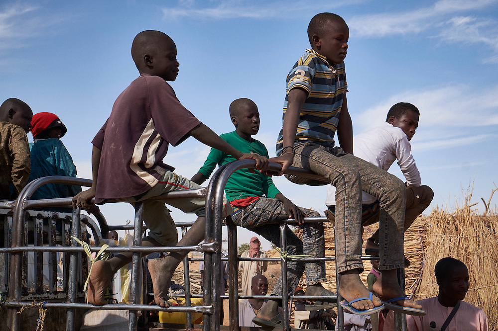 Boys sit on top of truck at a camp of internally displaced people near the village of Kouble by the side of the road on the highway outside of Diffa, Niger on February 17, 2016. The truck is departing to the nearby border where men will return to tend fields in their villages. The camp is made up of displaced people and refugees from villages along the border between Niger and Nigeria and who fled attacks from Boko Haram.