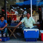 Benito Hernandez, has a little shop on the street in El Progreso.  He sits with his two sons, (L-R) Christian Hernandez and Junior Hernandez on February 11, 2017 in El Progreso, Honduras.  Benito lost two limbs when he was mirgrating to the United States through Mexico.  He was on the train when immigration officers came for him.  He fell off the train which severed the limbs.  He wife has since left him and his sufferring is greater as he can no longer work as many jobs as in the past.