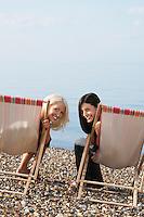 Two women sitting on deckchairs on beach portrait