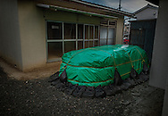 Radioactive soil is stored under a green tarpaulin after decontamination is parked in front of an unoccupied, and likely to remain unoccupied, apartment in Fukushima City.  Between 2cm - 5cm (0.8 - 2 inches) has been removed during decontamination to lower the ambient radioactivity 5 years after meltdowns triggered hydrogen explosions at Fukushima Daiichi Nuclear Power Plant 57 km (35.4 mi) away.  The radioactive cloud was blown right to the northwest over Fukushima, and then mountains to the west stopped it, diverting it to the southwest.