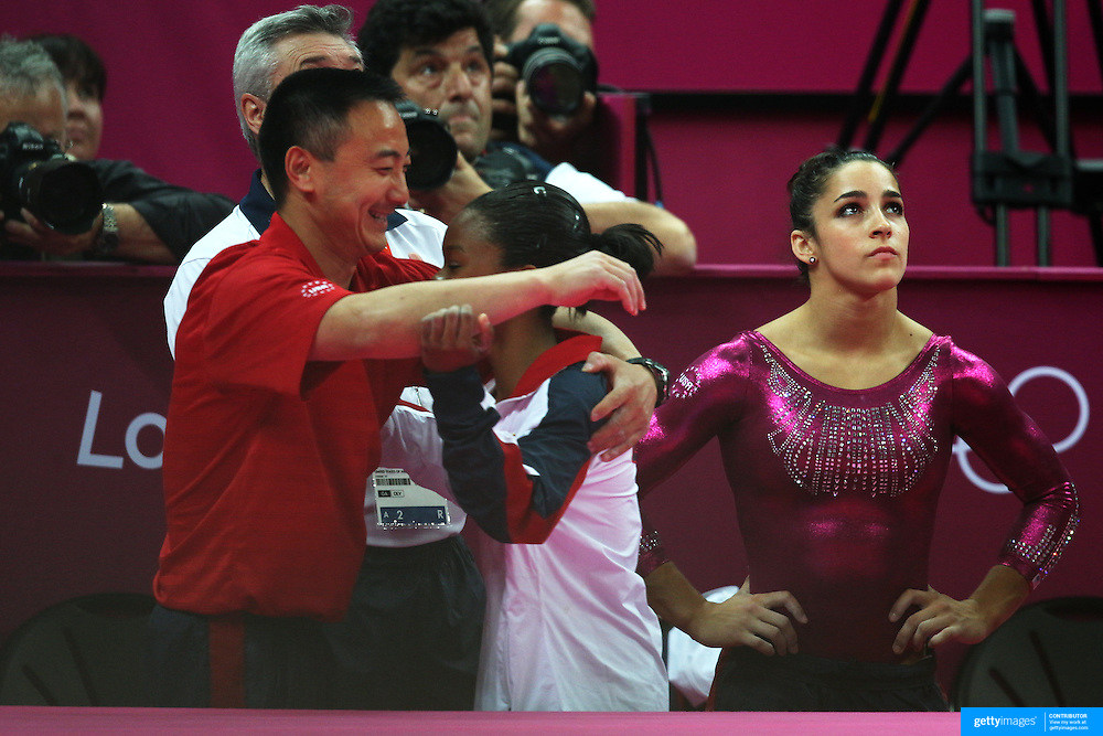 Gabrielle Douglas, USA,  with coach Liang Chow during her Gold medal performance in the Women's Individual All Round competition as team mate Alexandra Raisman, USA, reflects on her fourth place during the artistic gymnastic competition at North Greenwich Arena during the London 2012 Olympic games London, UK. 2nd August 2012. Photo Tim Clayton