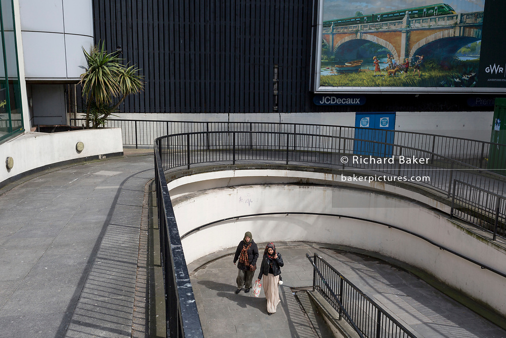 Locals walk in a concrete walkway beneath a travel billboard ad featuring an idyllic countryside scene for GWR railways at Elephant And Castle, on 3rd May 2018, in south London, UK.