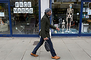 As the Coronovirus pandemic takes hold across the UK, with 53 cases now reported by health authorities, a man walks past the window of a medical equipment business in south London, displays a face masks sign and surgical masks on a skeleton mannequin, on 4th March 2020, in London, England.