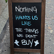 Blackboard humorous  store outdoor sign before Halloween. <br /> <br /> &quot;Nothing Hauts Us Like the Things we Don't Buy&quot;
