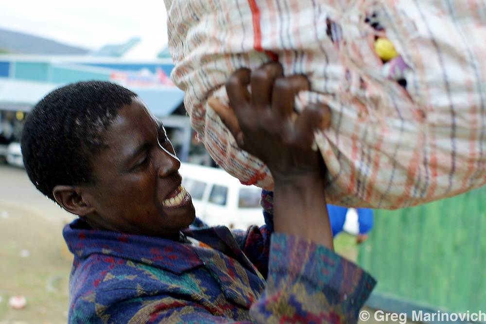 IPMG0918 Tugela Ferry, South Africa. Sithembe Mlambe (41) struggles to lift her stock of second hand clothes onto her head after a day of selling these clothes on the sidewalk in Tugela Ferry, KwaZulu Natal, South Africa, 27 October 2004.  Suffering from full-blown Aids, she was fortunate enough to be one of the first Aids sufferers to be included in an Anti-Retro Viral drug programme and has graually recovered her health, and manages to work and support her family, though the disease is never cured, just held at bay.  Greg Marinovich/South Photographs