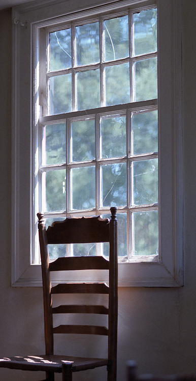 schoolhouse antique chair against bright streaming daylight through an antique window