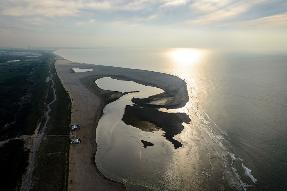 Nederland, Zuid-Holland, Gemeente Westland,  28-09-2014; Delflandse Kust ter hoogte van Ter Heijde en Monster. Maasvlakte aan de horizon, links de kassen van het Westland.<br /> De Zandmotor is den kunstmatig schiereiland ontstaan door het opspuiten van zand voor de kust. Wind, golven en stroming zullen het zand langs de kust verspreiden waardoor breder stranden en duinen ontstaan. De zandmotor is een experiment in het kader van kustonderhoud en kustverdediging. <br /> Sand Engine, artificial peninsula build by the raising of sand for the coast of Ter Heijde (near the Hague). Wind, waves and currents will distribute the sand along the coast yielding wider beaches and dunes along the coastline. The Sand Engine is a experiment for coastal maintenance of coastal defense.<br /> luchtfoto (toeslag op standard tarieven);<br /> aerial photo (additional fee required);<br /> copyright foto/photo Siebe Swart