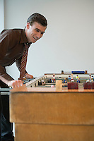 Young man playing table football in game room