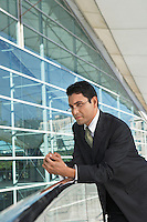Businessman leaning on railing outside office building