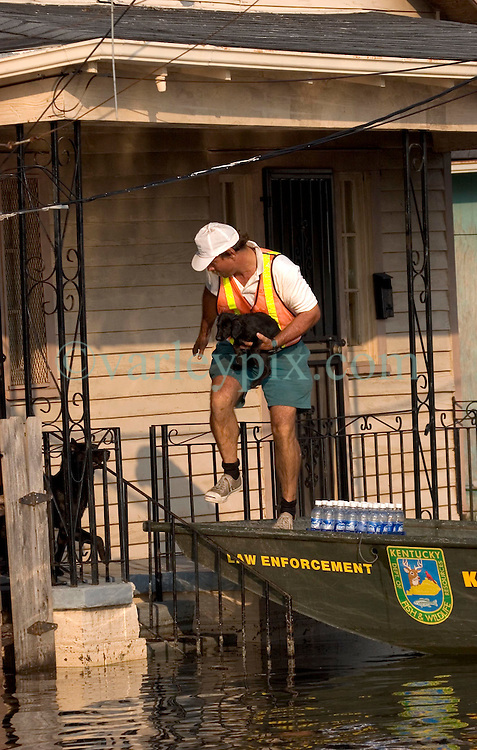 05 Sept  2005. New Orleans, Louisiana. Post hurricane Katrina.<br /> Animal rescue boat. Local man Jimmy Delery assists the The Kentucky Dept of Fish and Wildlife resources team as he rescues animals from the devastating floods in Uptown New Orleans.<br /> Photo; &copy;Charlie Varley/varleypix.com