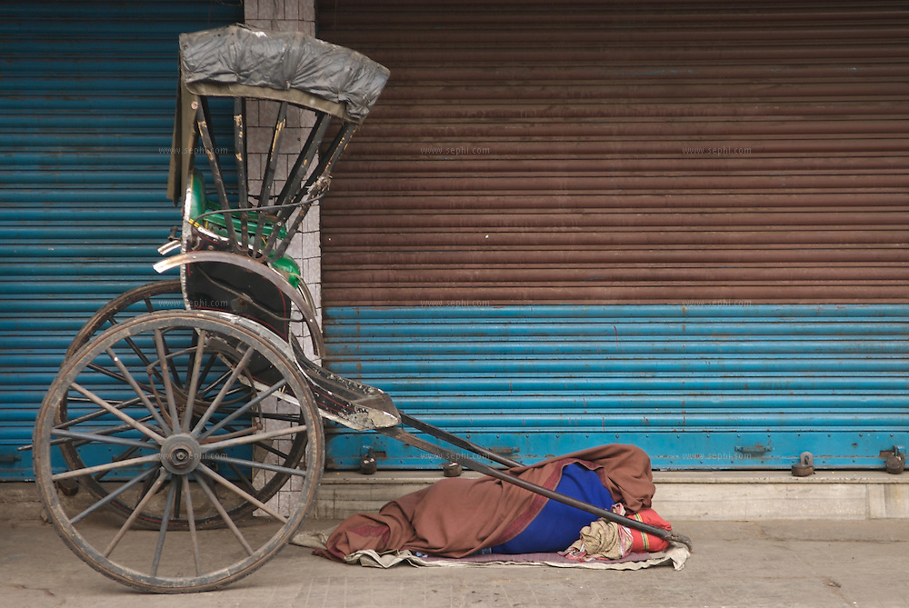 "A rickshaw puller sleaping next to his vehicle near 'New Market' in Kolkata...The hand-pulled rickshaw of Calcutta, immortalised by Dominic Lapierre's famous novel, City of Joy, will soon be a part of the history books as a bill passed by the West Bengal state assembly described the centuries-old mode of transport as ""inhumane."".The future of about 18,000 rickshaw pullers in the city, earning an avarage daily wages of about 100 rupees ($2.5).is unclear as they call for a compensation package to help them rehabilitate into alternative jobs."