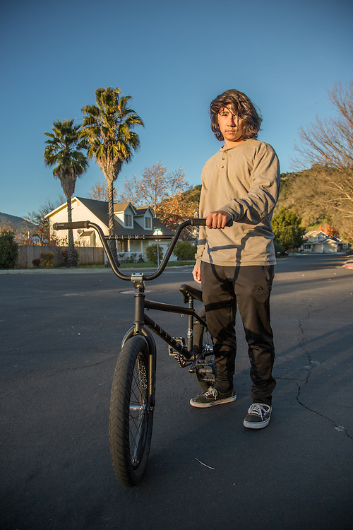 """My bike has a flat...I'm going to a friend's house to fix it.""  Fifteen year old Gabe Sullivan near his home in Calistoga."