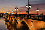 The Pont de Pierre at night, built 1810-22 under Napoleon I by engineers Claude Deschamps et Jean-Baptiste Basilide Billaudel, over the river Garonne, Bordeaux, Aquitaine, France. The stone and brick bridge links the town centre with the La Bastide district, is 487m long and is constructed on 17 arches held by 16 pillars. It was originally built by 4,000 workers and was widened in 1954. Picture by Manuel Cohen