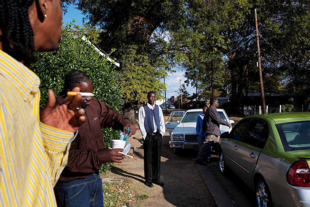 """Young men loiter on the corner of Young and Pelican after the funeral of Demetrius """"Butta"""" Anderson, 18, in the  Baptist Town neighborhood of Greenwood, Mississippi on Friday, November 5, 2010. As the funeral wrapped up many of Butta's friends gathered on the corner for a block party to celebrate his life."""