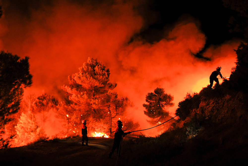 Firefighters of Alcoy and Elda try to extinguish a fire in Torre de Macanes near Alicante, on August 13, 2012. One person was killed and three injured Sunday as firefighters battled wildfires across Spain, authorities said, the latest victims in a sweltering summer of forest blazes. AFP PHOTO/Pedro ARMESTRE