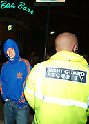 Youth in hoodie looking round security guard, Kent, UK 2005, model released