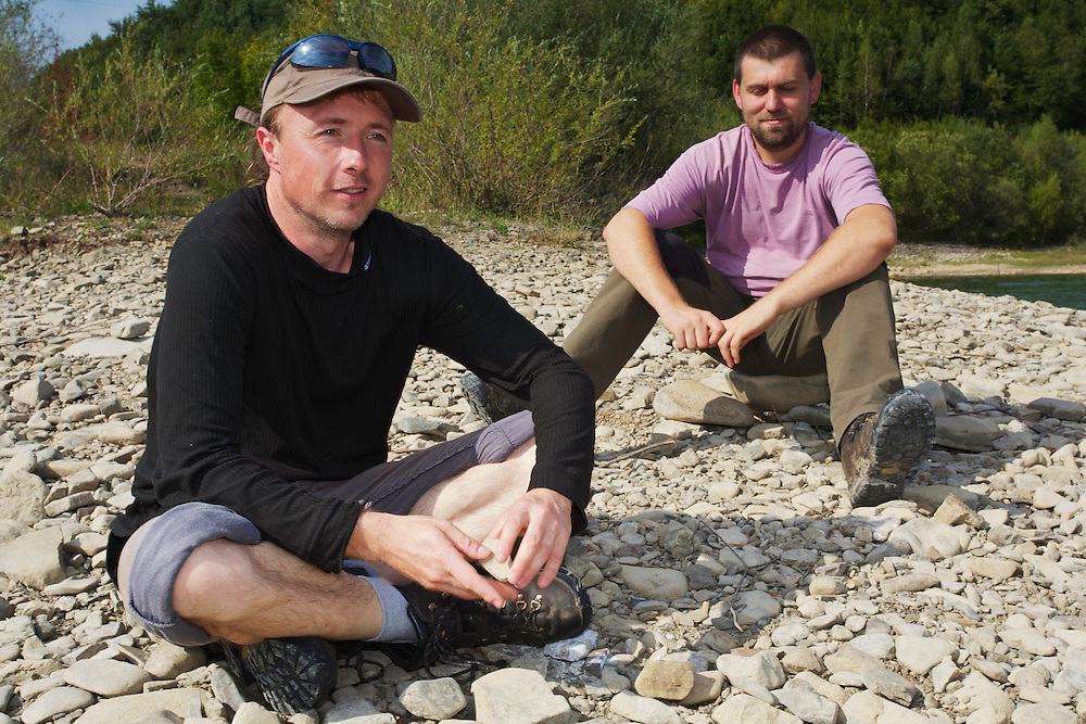 "Kamil Soos (left) and Viliam Bartus, members of the conservation NGO ""Wolf"", taking a rest on the banks of Starina Reservoir. Jalova, Slovakia."