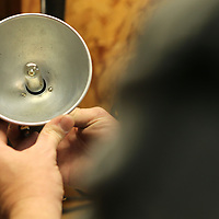 Once all is done, Hubbard places the reflector on the flash head and puts a bulb in the socket.