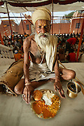 "Sitarani Tyaagi, an ascetic Hindu priest, with his typical day's worth of food at an ashram in Ujjain, India. (From the book What I Eat; Around the World in 80  Diets.)  The caloric value of his typical day's worth of food in the month of April was 1000 kcals. He is 70 years of age; 5 feet, 6 inches tall; and 103 pounds. Sitarani Tyaagi is one of thousands of ascetic Hindu priests?called Sadhus?that walk the country of India and receive food from observant Hindus. Generally, he eats one meal per day and has water for the other two meals. He has a small pot that he carries with him for water. Offer him more food than a plateful, and he will kindly say, ""no thanks.""  MODEL RELEASED."