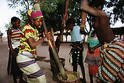 Women and girls pound millet grain to make flour for porridge in Djenne, Mali. Talking and singing often accompany this very physical task. Material World Project.