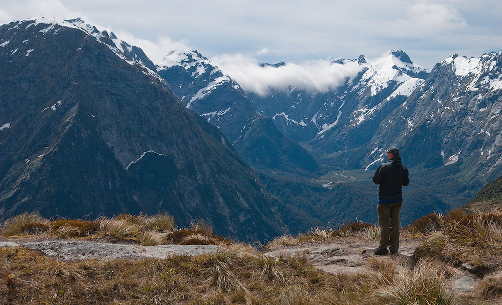 A walker takes in the view from Mackinnon Pass across to Mount Pillans, Mount Edgar and Green Valley, New Zealand
