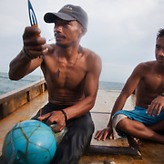 Abelino fixes the nest in his down-time while Joseph looks on. Joseph is 17 and works like his father did on the sea as a fisherman. The catch of the day is hauled in by the entire crew to be sorted out on deck and taken straight to the market in Hinigaran. The catch that day made the crew $12.00 each( Captain Joan $24.00) One day a week Joseph goes to Alternative Learning schooling provided by Quidan-Kaisahan.  Quidan-Kaisahan is a charity working in Negros Occidental in the Philippines. Their aim is to keep children out of work to secure them education.