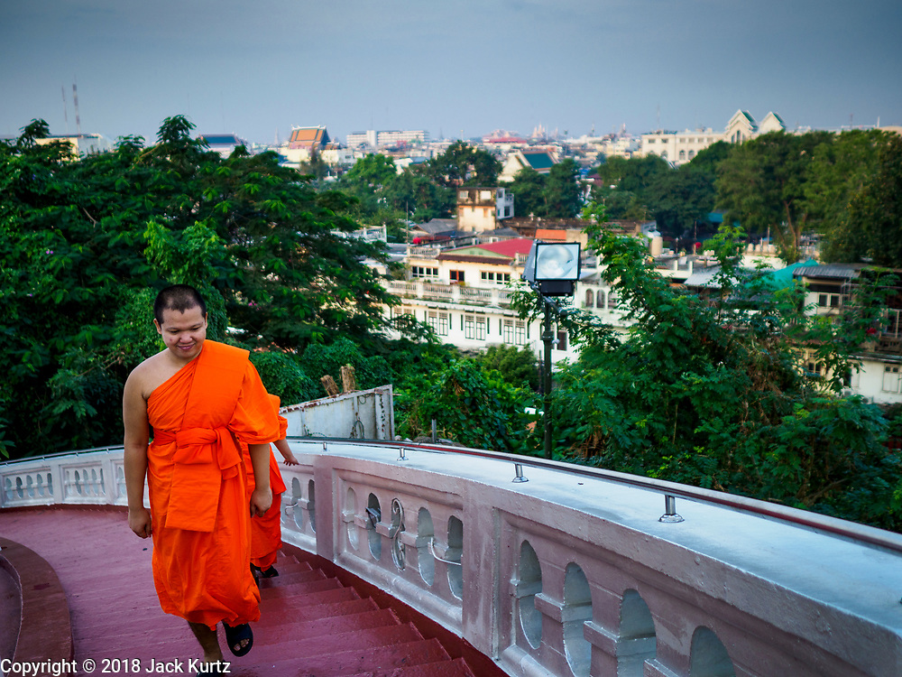 15 NOVEMBER 2018 - BANGKOK, THAILAND:  Monks walk to the top of Wat Saket, also called the Golden Mount, for the red cloth ceremony. Wat Saket is on a man-made hill in the historic section of Bangkok. The temple has golden spire that is 260 feet high, which was the highest point in Bangkok for more than 100 years. The temple construction began in the 1800s during the reign of King Rama III and was completed in the reign of King Rama IV. A  red cloth (reminiscent of a monk's robe) is placed around the chedi at the top of  Golden Mount during the weeks leading up to the Thai holy day of Loy Krathong, which is November 22 this year.  PHOTO BY JACK KURTZ