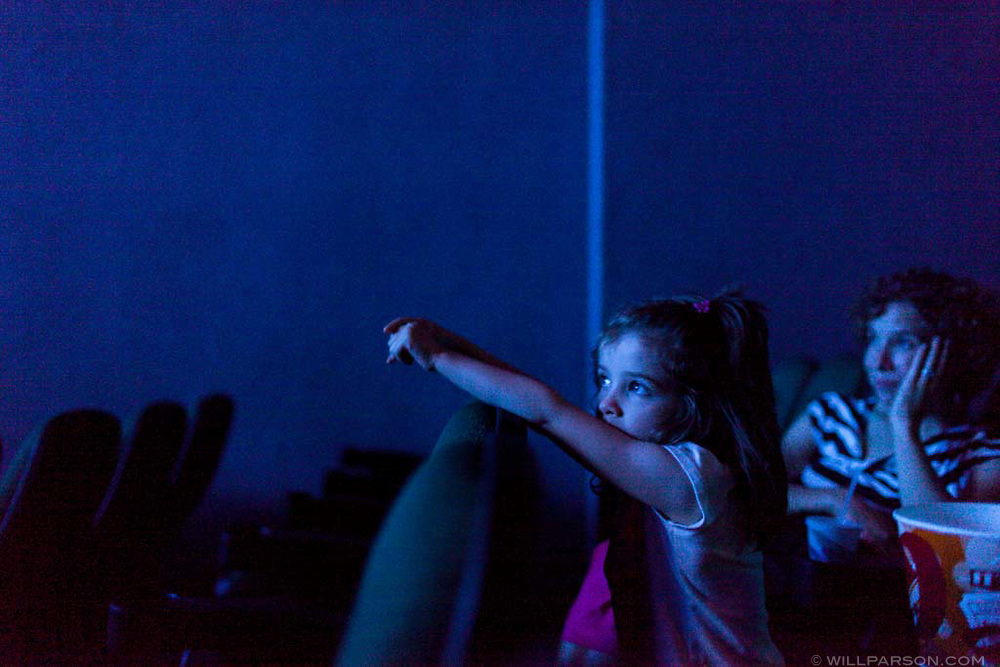 "Harper Lewis, 5, of Hanover, N.H., watches from the edge of her seat during a screening of a singalong version of the Disney film Frozen with her mother Elizabeth Cascio and several friends at Nugget Theaters in Hanover on June 23, 2014. Cascio estimates that Lewis has seen the movie ""about ten"" times. (Valley News - Will Parson)"