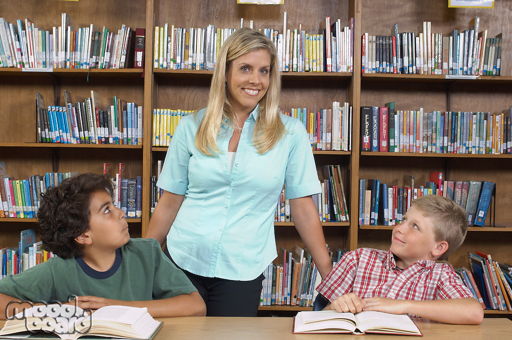 Two school boys with teacher in library
