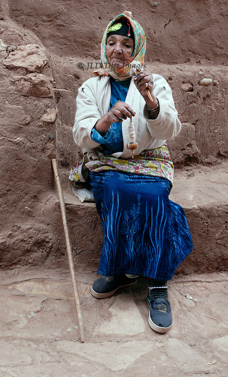 Elderly woman spinning wool on a spindle hanging from her hands.  She sits on a mud brick ledge in the kasbah of Aid Benhaddou, self-consciously picturesque, in hopes of a tip.