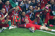 Portugal Forward Cristiano Ronaldo celebrates on the grass with his teammates during the Euro 2016 final between Portugal and France at Stade de France, Saint-Denis, Paris, France on 10 July 2016. Photo by Phil Duncan.