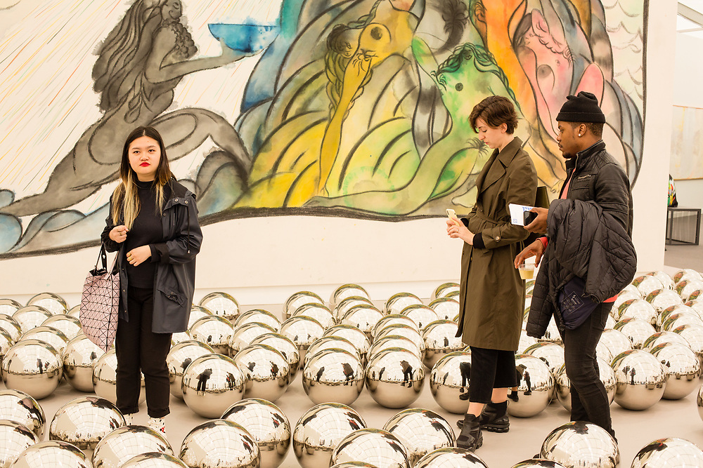"New York, NY - May 3, 2019. Spectators wander through Yayoi Kusame's ""Narcissus Garden"" full of stainless steel spheres, in front of Chris Olifi's oil ""to take and to give"" in the Victoria Miro Gallery at the Frieze Art Fair on New York City's Randalls Island."