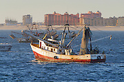 19 NOVEMBER 2002 - PUERTO PENASCO, SONORA, MEXICO: A fishing trawler heads out to the Sea of Cortez past the new Sonora Spa in Puerto Penasco, Tuesday, November 19. Puerto Penasco used to be a quiet fishing village but is now contending with explosive growth in its tourism industry. The Sonora Spa is one of the newest and largest resorts going up in Puerto Penasco.   PHOTO BY JACK KURTZ