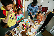 Breakfast at the Madsen family's home in Cap Hope village, Greenland, has a little bit of everything. (From the book What I Eat: Around the World in 80 Diets.) From sandwiches to cereal, everyone helps themselves to their morning meal. Emil (in blue shirt) stands in between his daughter Belissa and nephew Julian, 10. Abraham stands to the left of Julian, and Erika sits on the couch behind. This is an especially big and varied breakfast because Emil had been on a hunting trip for a week and had just returned the night before, after collecting money in Ittoqqortoormiit, buying supplies in the store there and returning to his village on his dogsled (1.5 hours).