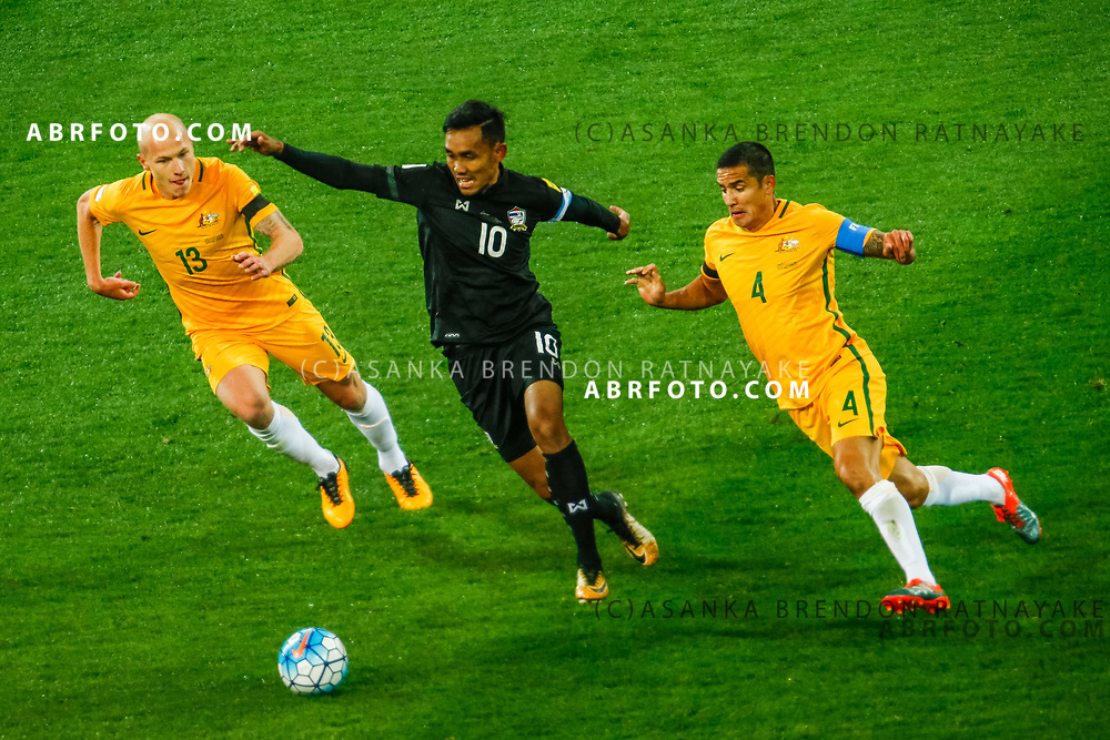 MELBOURNE, AUSTRALIA - SEPTEMBER 5 : Teerasil Dangda of Thailand controls the ball away from Aaron Mooy of the Australia Socceroos and Tim Cahill of the Australia Socceroos during the Stage 3 Group World Cup Football Qualifiers between Australia Vs Thailand at the Melbourne Rectangular Stadium, Melbourne, Australia 5 September 2017.